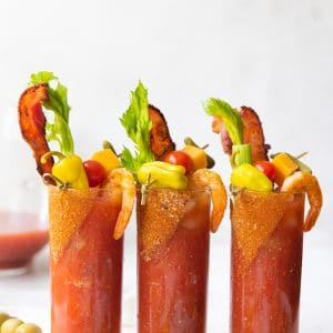 spicy bloody marys in glasses with bacon and celery