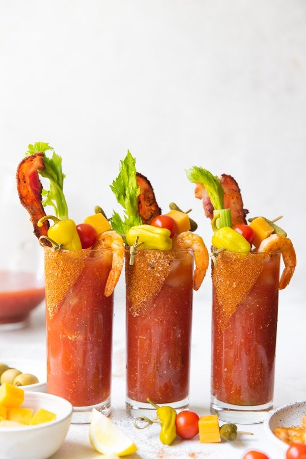 bloody marys in highball glasses with celery and bacon