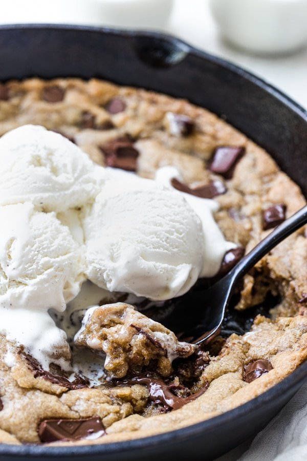 a cookie in a cast iron skillet with ice cream on top
