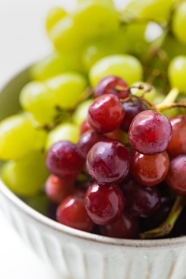 a bowl of red and green grapes