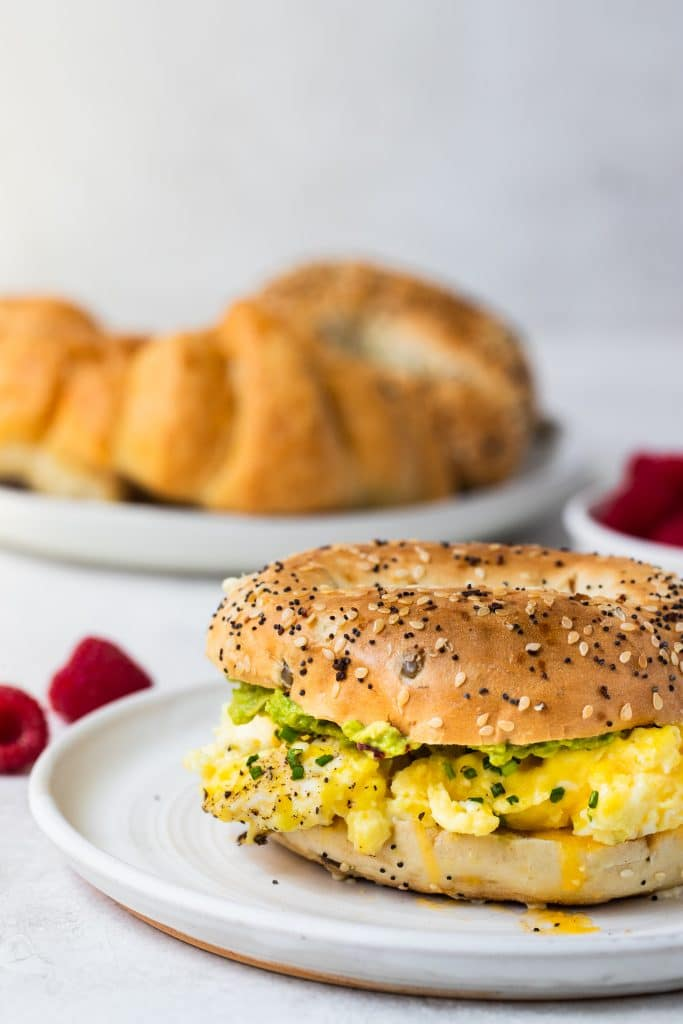 creamy scrambled eggs on a bagel on a white plate