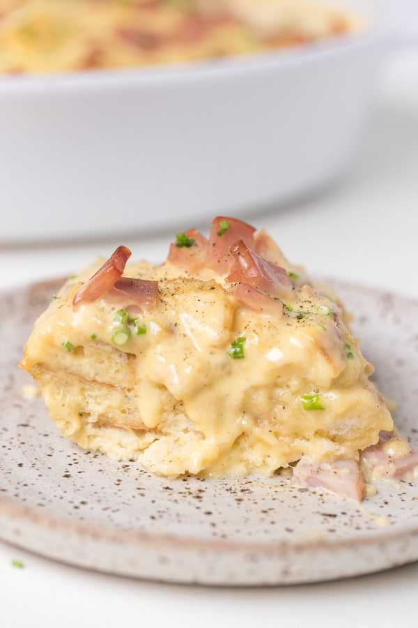 casserole on a speckled white plate with hollandaise on top