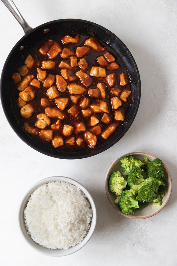 chicken in a skillet, cooked rice in a white bowl and steamed broccoli