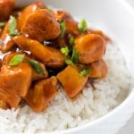 chicken with sauce on top of rice in a white bowl