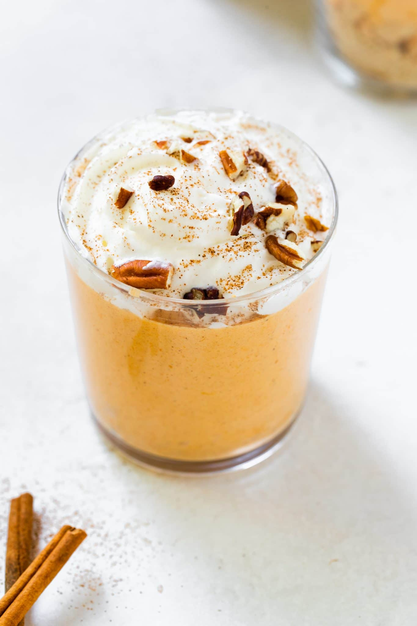 pumpkin mousse in a glass topped with whipped cream and pecans