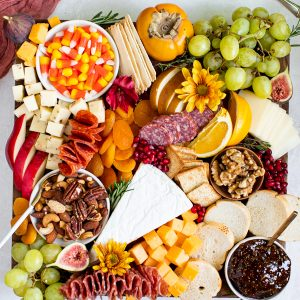 fruits, meats and cheese on a cutting board