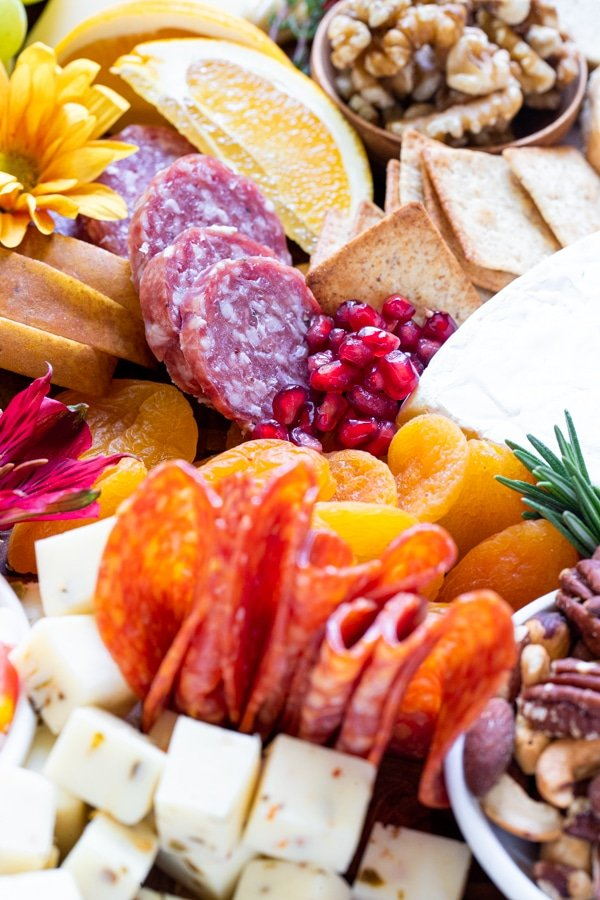 a charcuterie board filled with fruits, meats and cheese on a wood cutting board