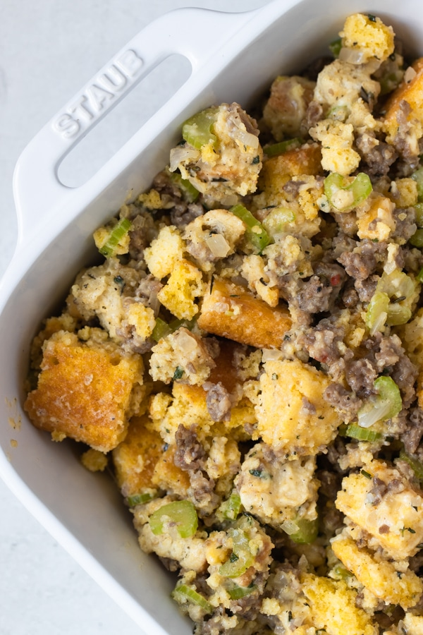 cornbread stuffing made with sausage and herbs in a white casserole dish