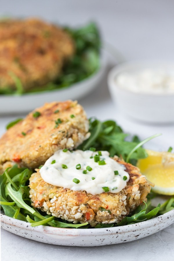 crab cakes on a plate with creamy special sauce on top garnished with chives