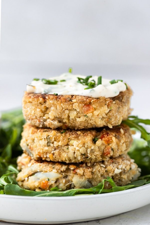 crab cakes with special sauce on a white plate with arugula and