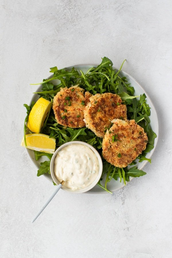 crab cakes on a white plate with arugula