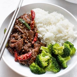 Mongolian beef with rice and broccoli in a white bowl