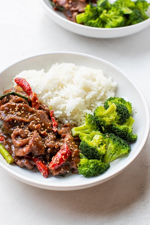 Mongolian Beef in a white bowl with rice and broccoli