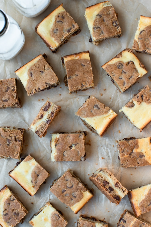 Chocolate Chip Cookie Cheesecake Bars on parchment paper cut into small squares
