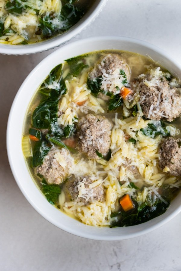 Italian wedding soup in a white bowl topped with cheese