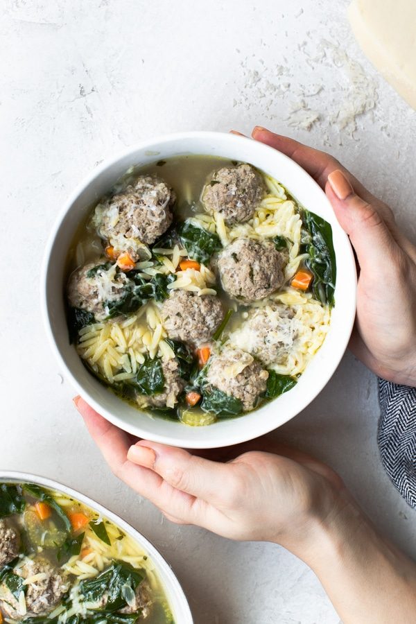 A woman's hands holding a white bowl filled with Italian wedding soup