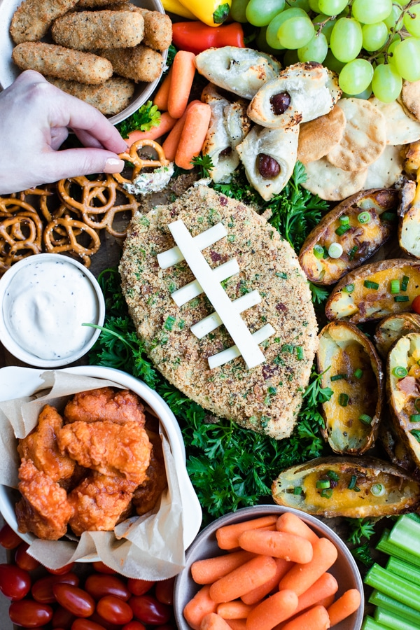 a jalapeno popper cheese ball on a cutting board with game day snack foods