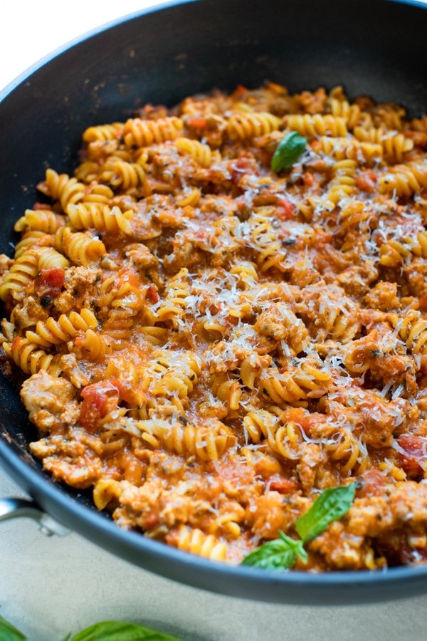 a skillet filled with rotini pasta and ground turkey