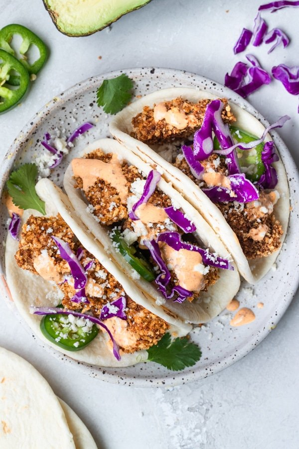 mahi mahi tacos on a white speckled plate