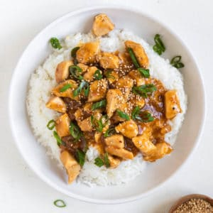 orange chicken on top of white rice in a white bowl
