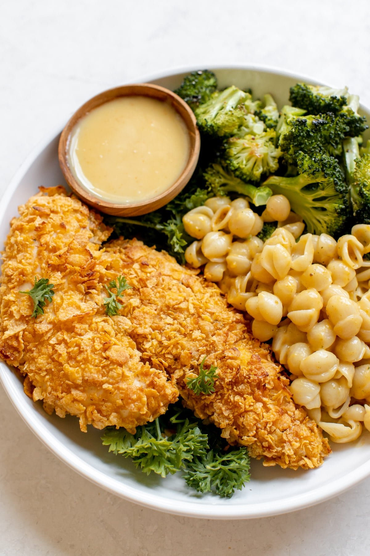 chicken tenders, mac and cheese and broccoli in a white plate