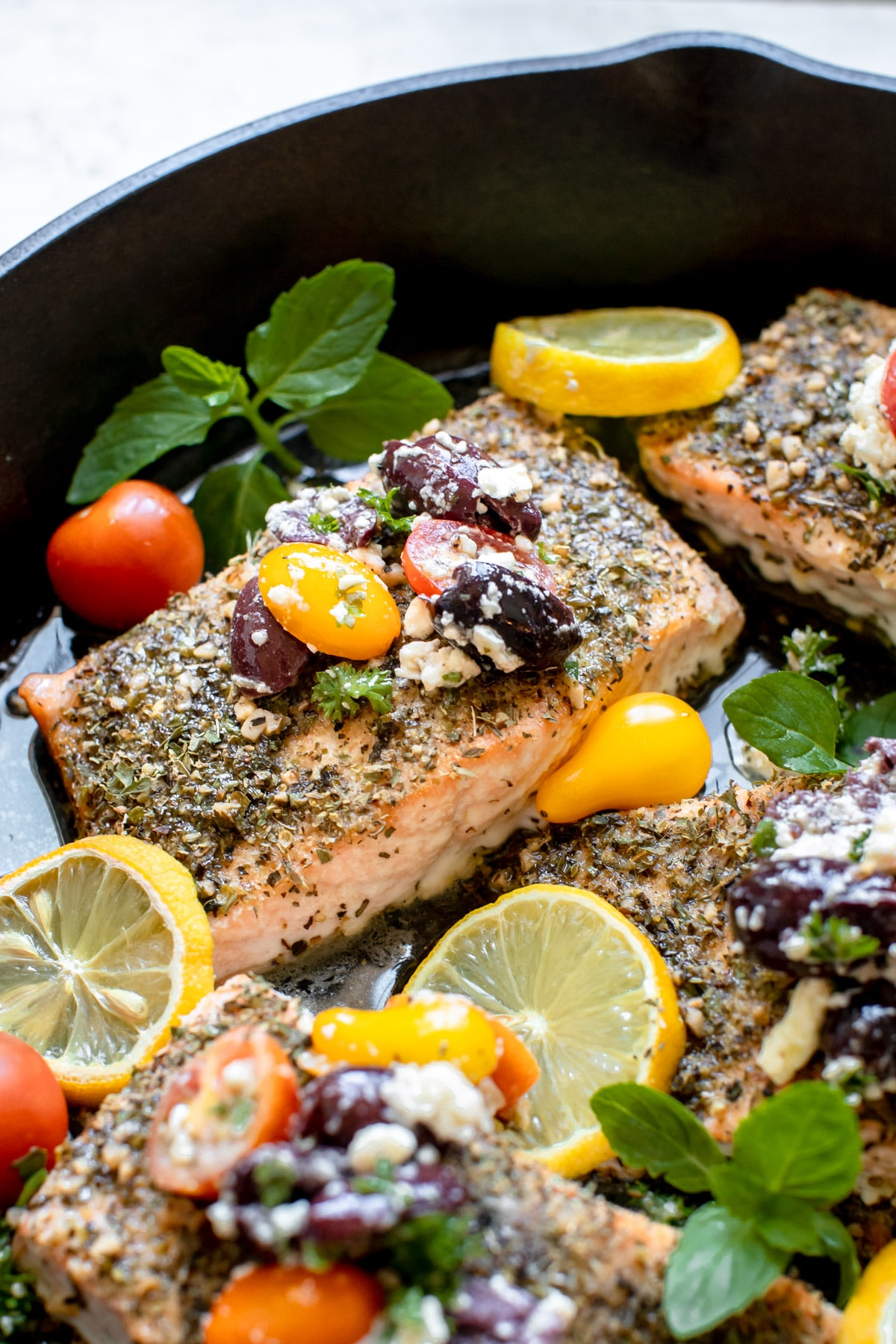 cooked mediterranean salmon with tomatoes and kalamata olives on top in a cast iron pan