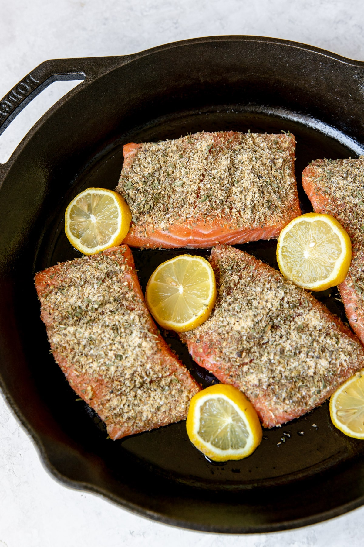 fresh salmon fillets in a cast iron skillet with lemon slices
