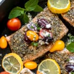 salmon in a cast iron skillet with tomatoes and kalamata olives