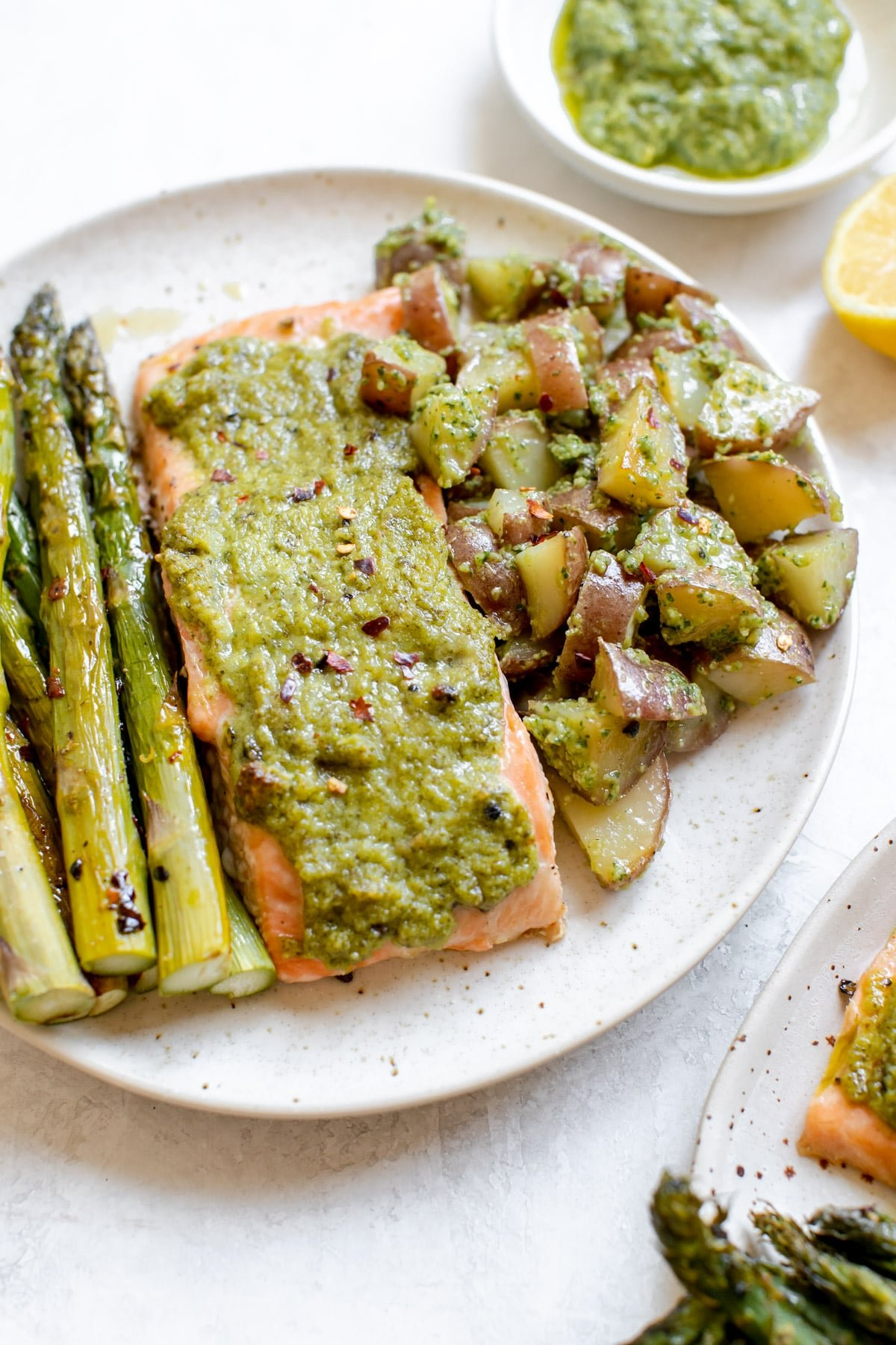 salmon on a white plate with pesto on top