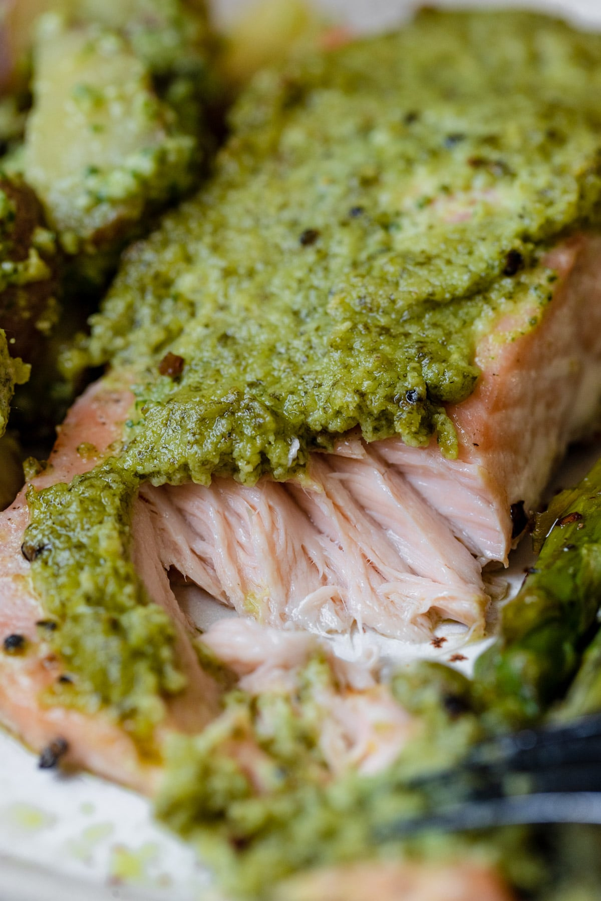 an up close image of salmon topped with a homemade pesto on a sheet pan