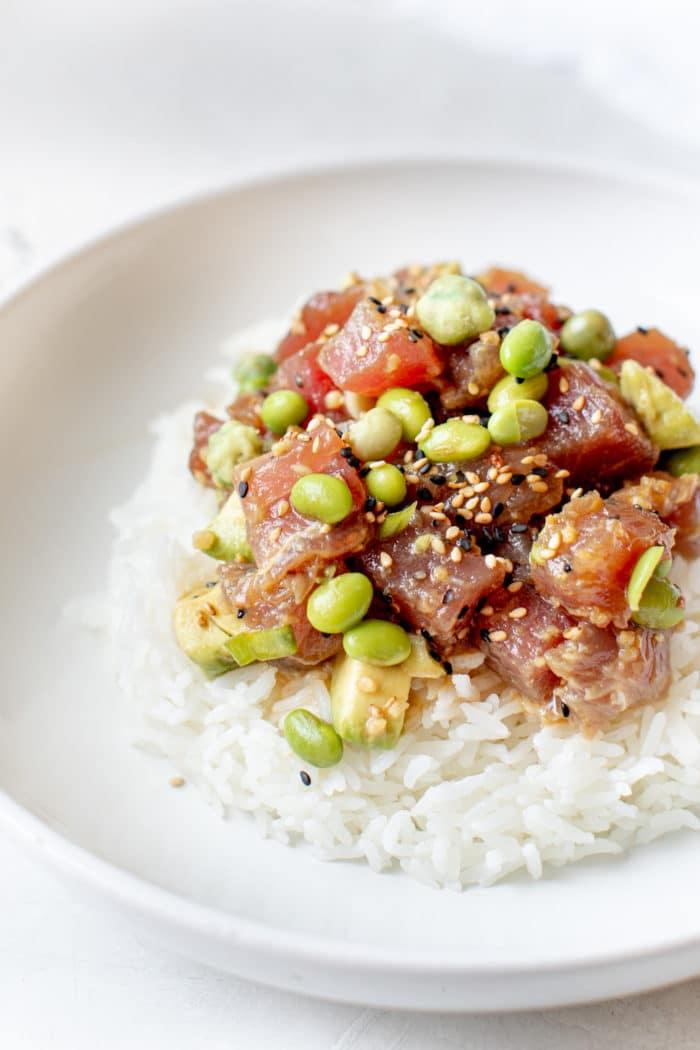 ahi tuna poke on top of white rice in a white bowl