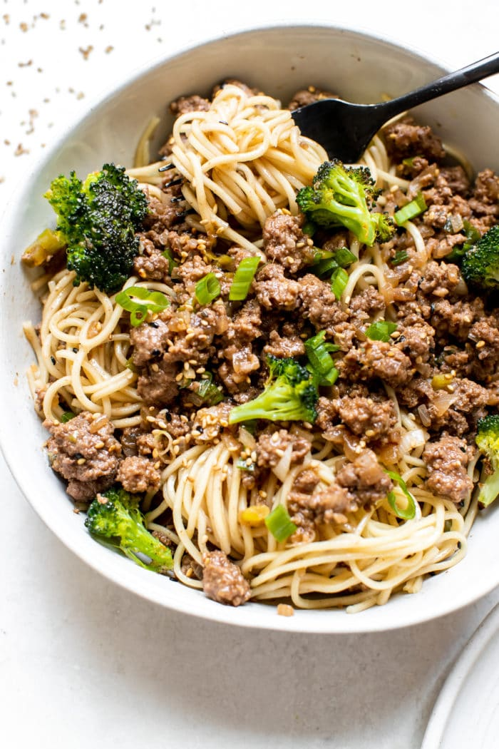 ground beef over noodles in a white bowl