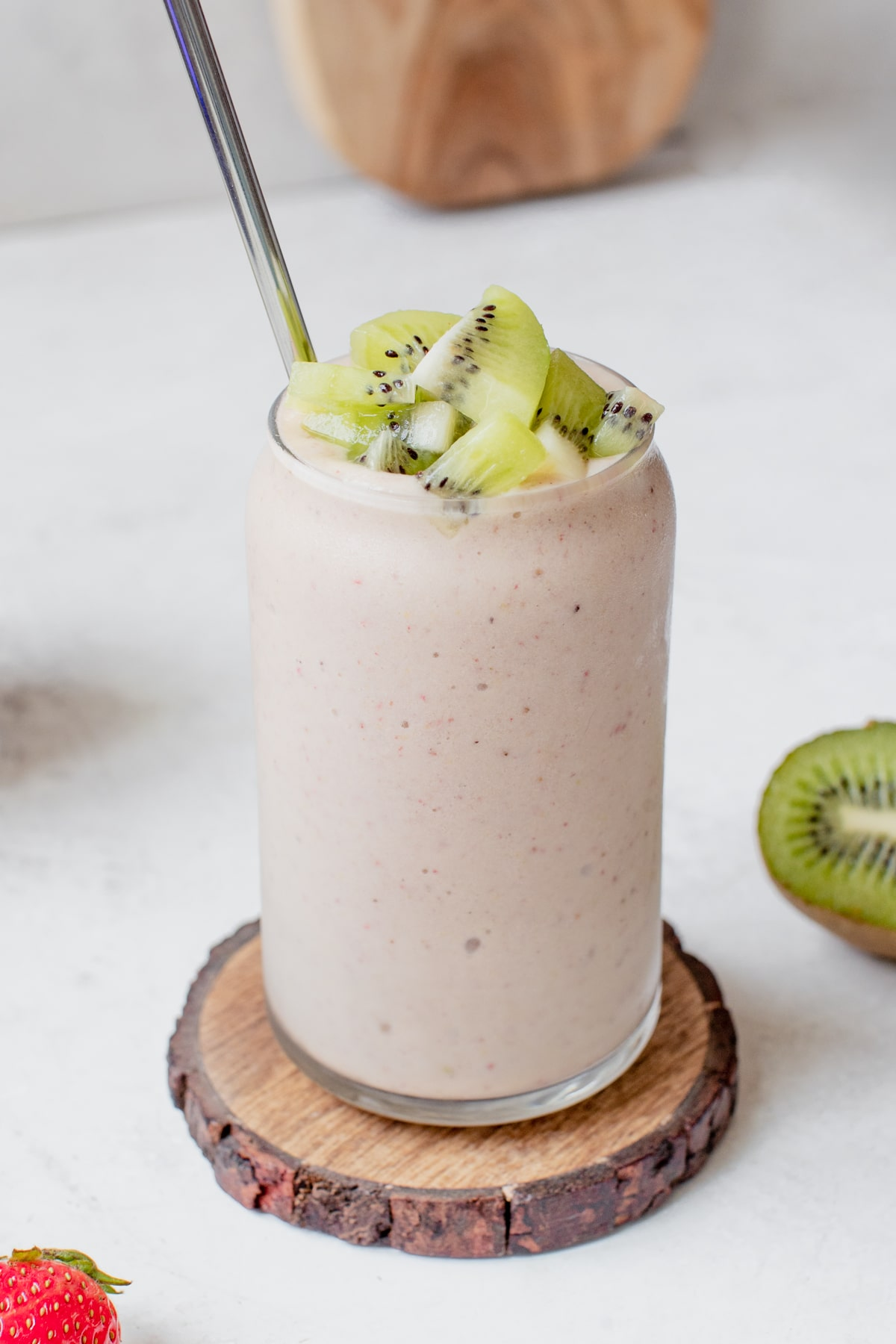 strawberry kiwi smoothie in a glass topped with diced fresh kiwi chunks
