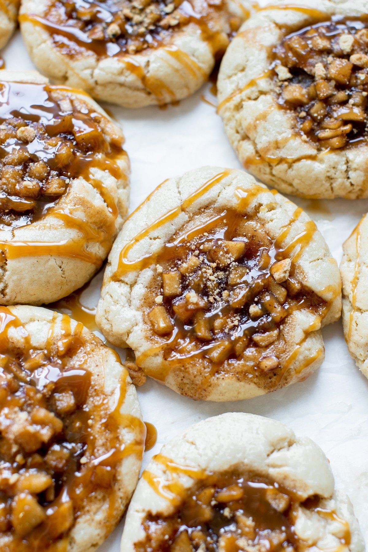 sugar cookies with an apple pie filling in the center with a caramel drizzle on top