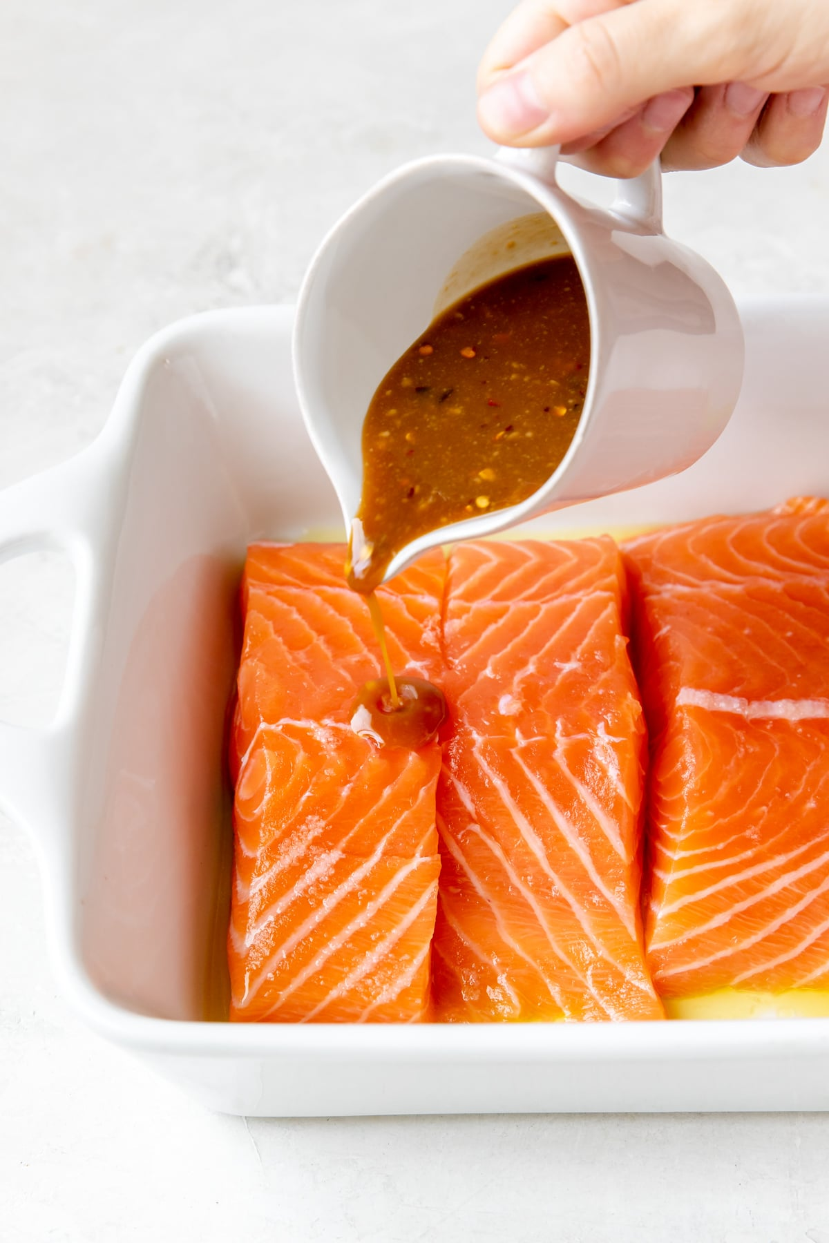 brown sugar miso sauce being poured onto fresh salmon fillets in a white baking dish