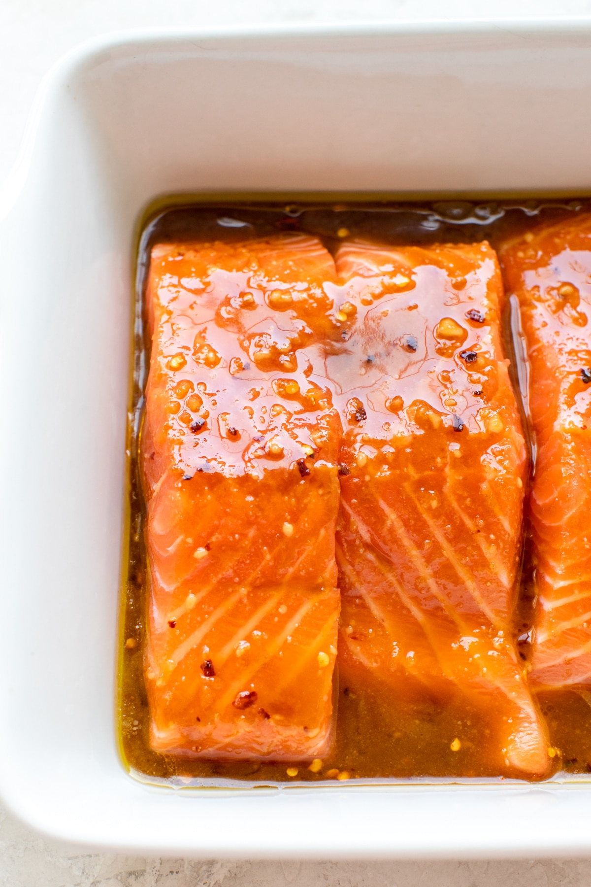 salmon in a white baking dish with a brown sugar glaze poured on top