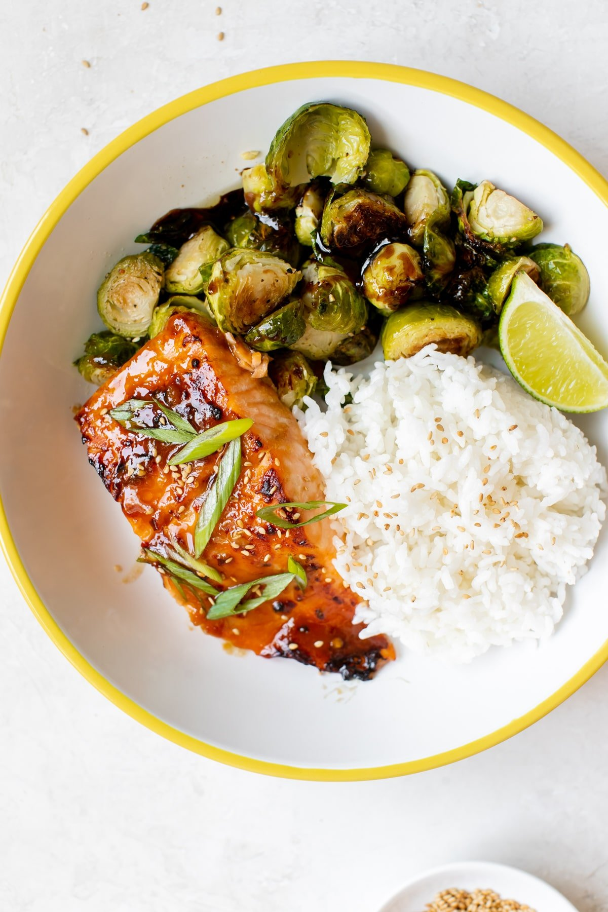 salmon, white rice and roasted brussels in a white bowl with yellow trim