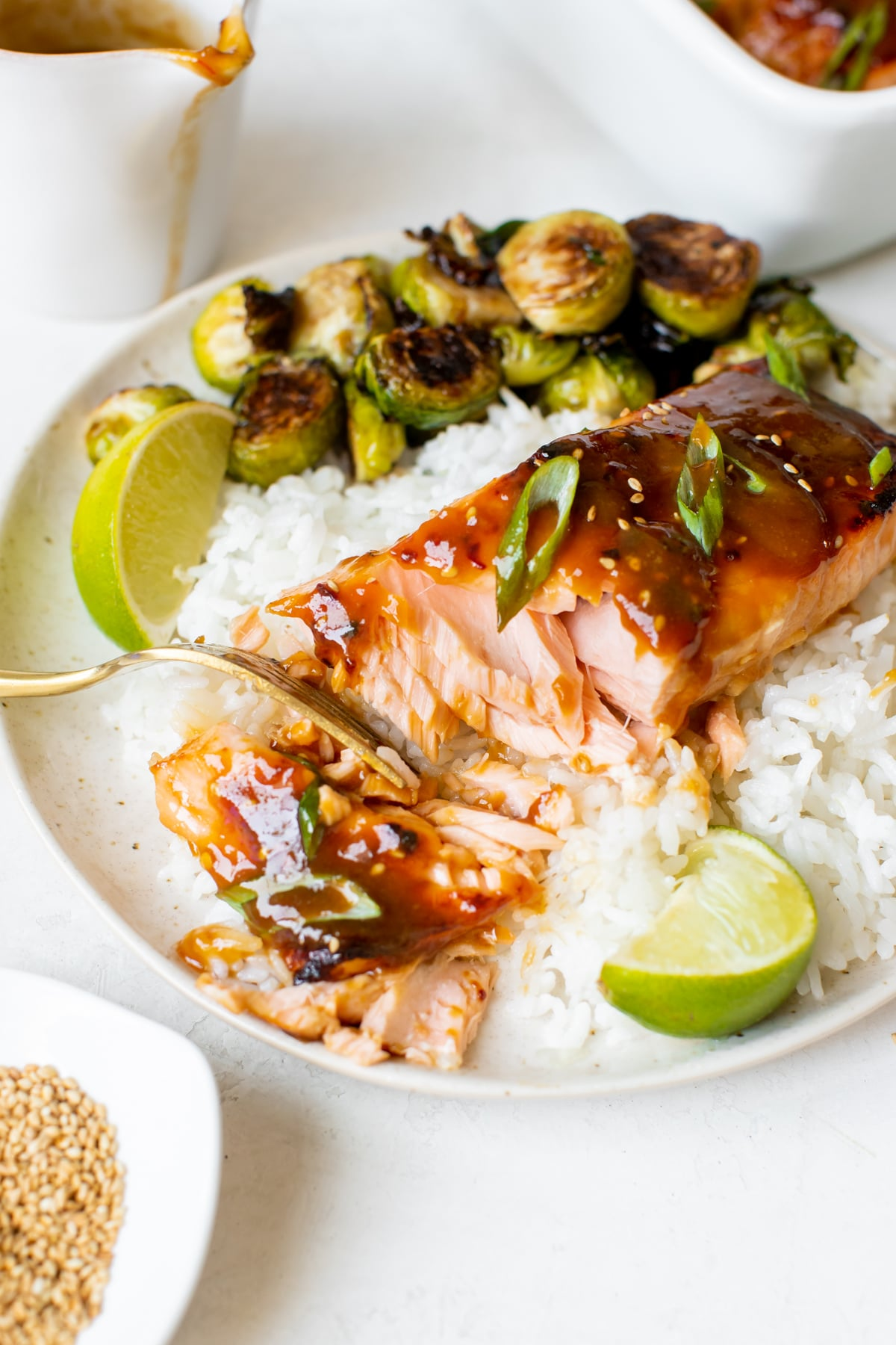 salmon with a gold fork flaking off a bite on a white plate with white rice and roasted brussels
