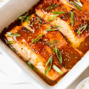 salmon in a white oven safe baking dish garnished with green onions and toasted sesame seeds