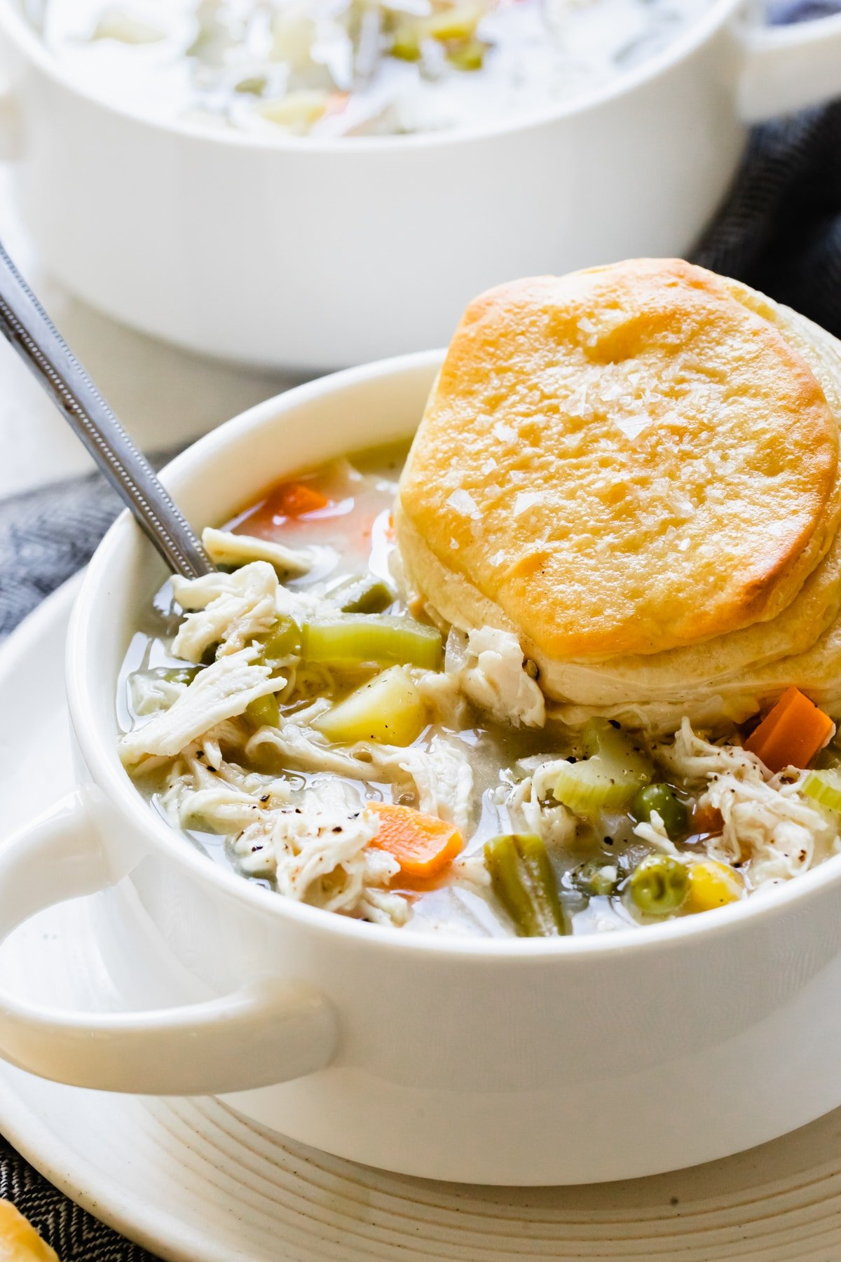 pot pie soup with chicken in a white soup bowl with a flaky biscuit on top