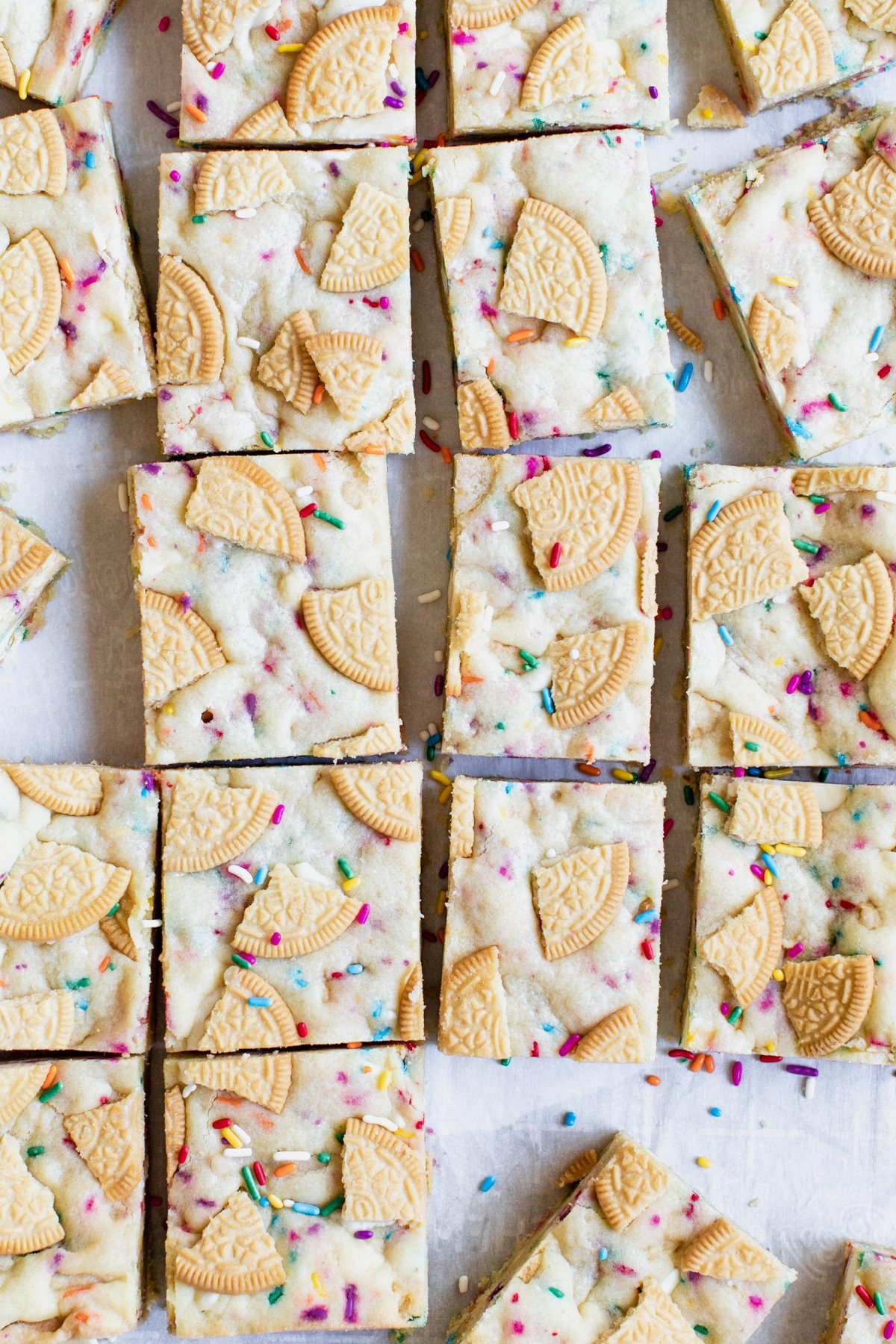 cookie bars on parchment paper with sprinkles and golden oreos