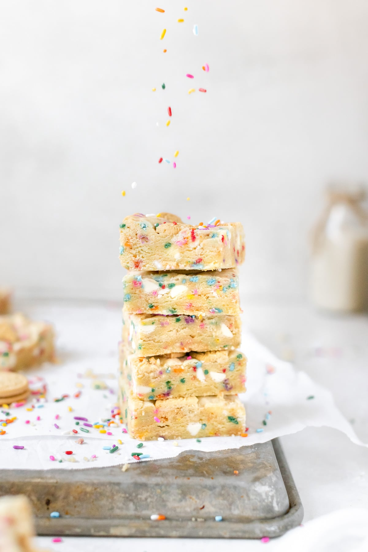 a stack of funfetti cookie bars on parchment paper