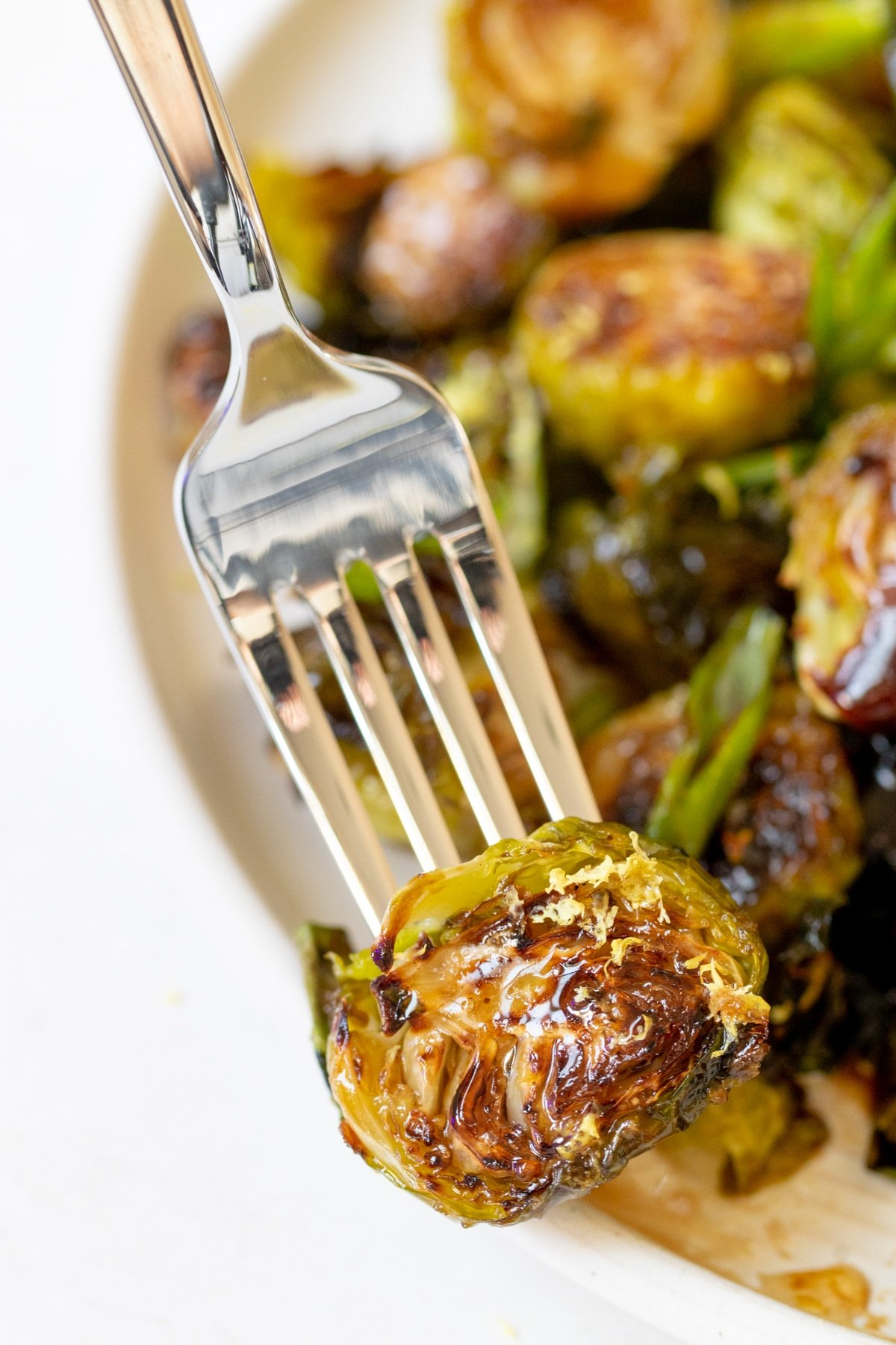 a fork inserted into a roasted brussels sprout