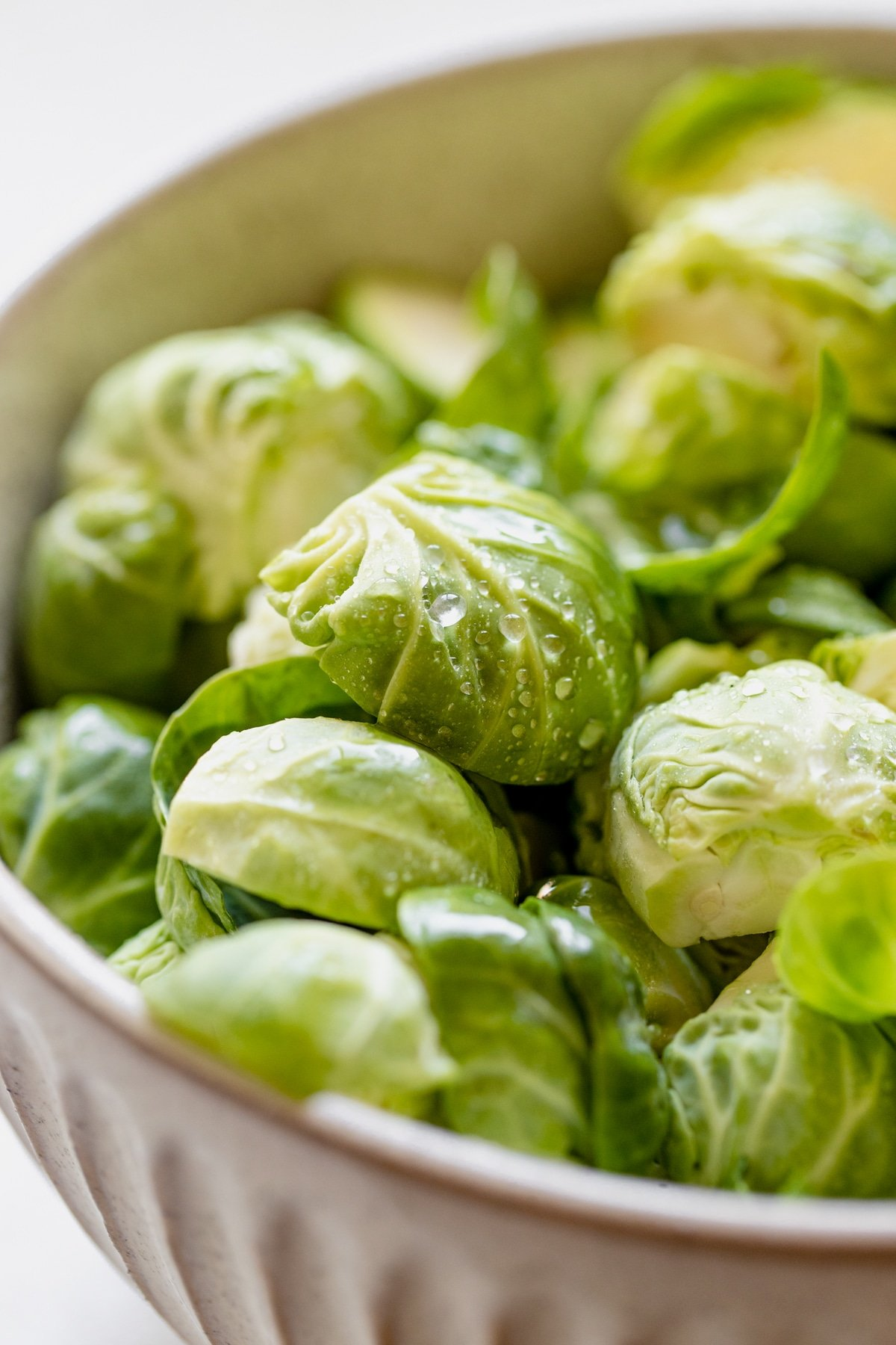 fresh brussels sprouts cut in half in a bowl
