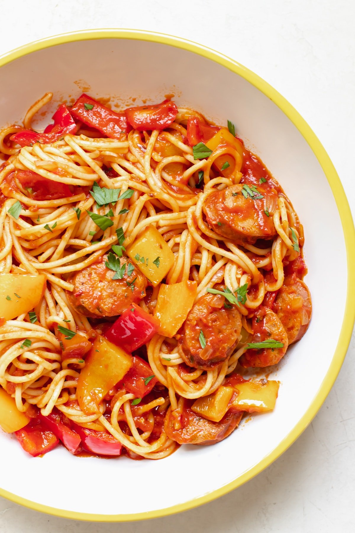 spaghetti and sausage in a white bowl topped with parsley