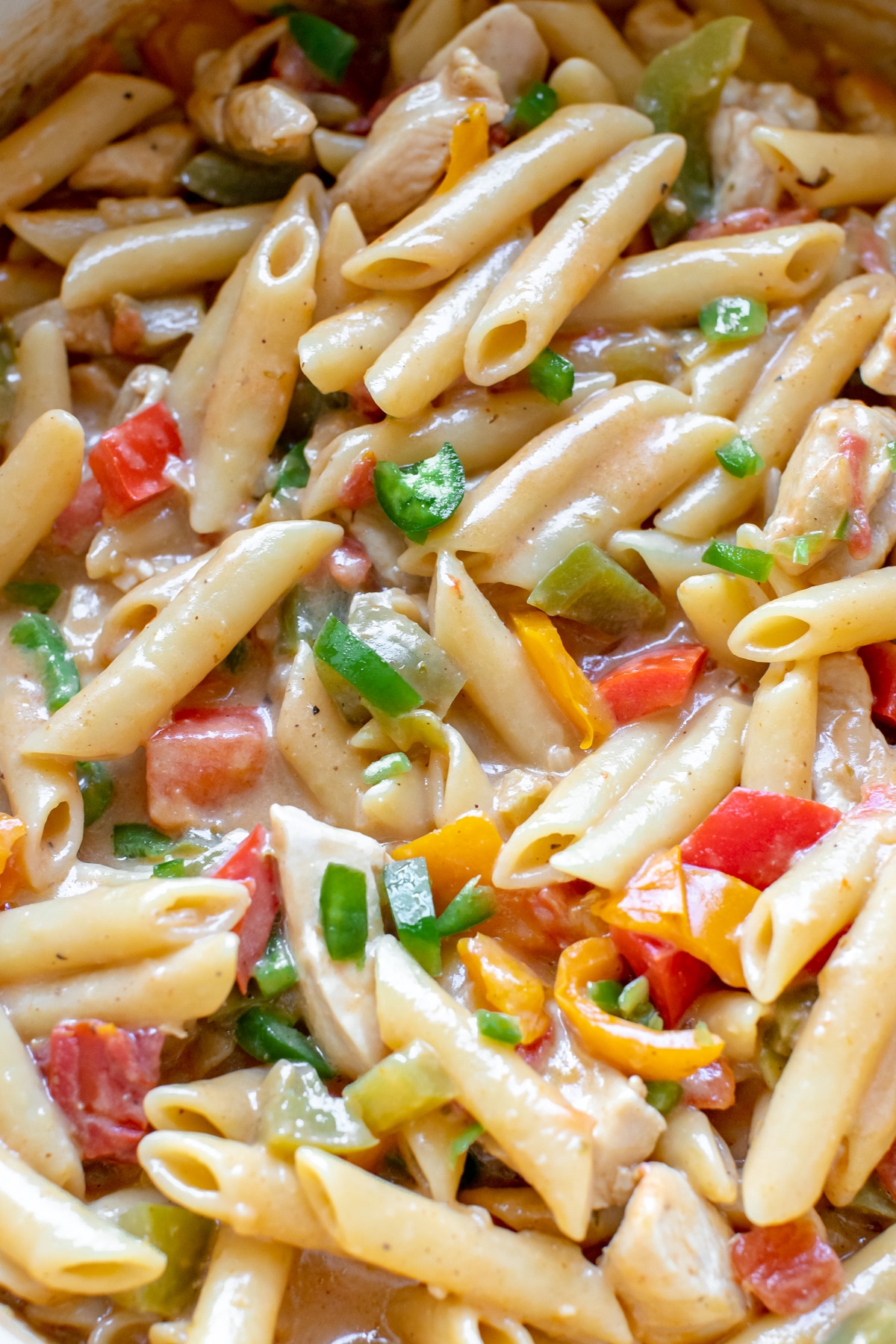 an up close photo of penne pasta with chicken, bell peppers and jalapeno