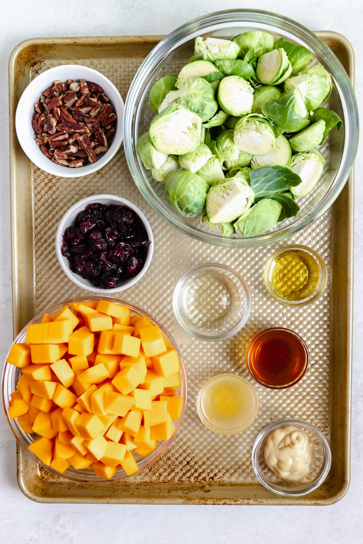 ingredients needed to make roasted brussels sprouts and butternut squash in small dishes on a gold sheet pan