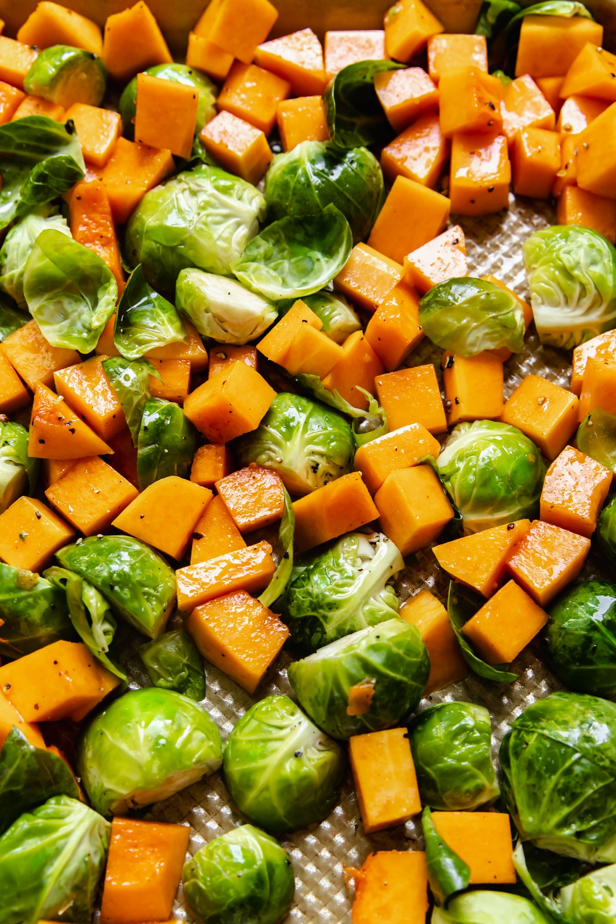 chopped vegetables on a gold sheet pan tossed in olive oil, salt and pepper