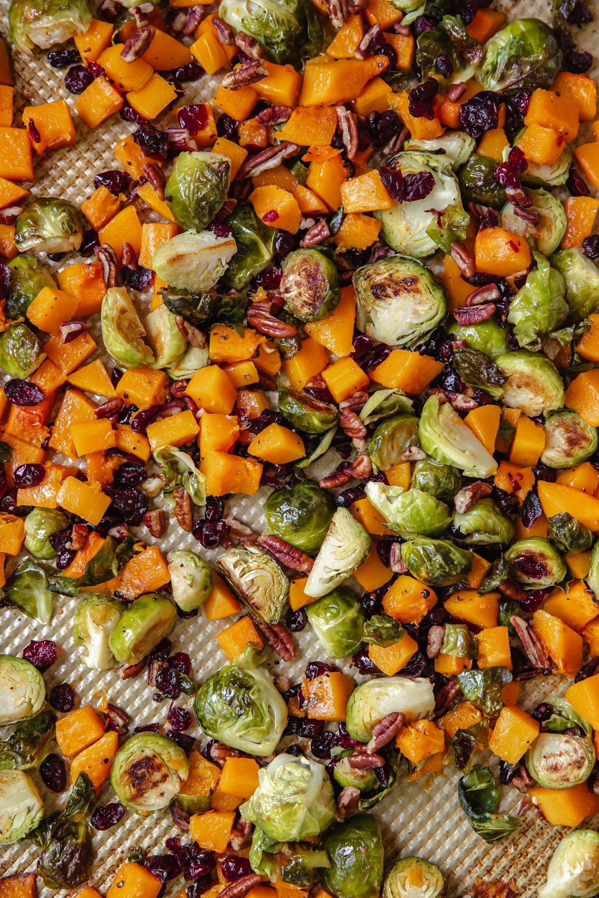 veggies on a gold sheet pan garnished with chopped pecans and dried cranberries